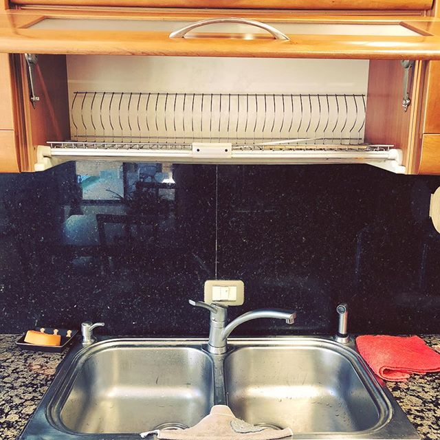 The cabinet over my in-laws' kitchen sink is a drying rack and I think it may be my new most coveted household thing.