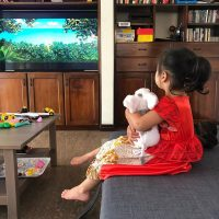 a little girl sitting in front of a television