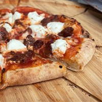 a slice of pizza sitting on top of a wooden cutting board